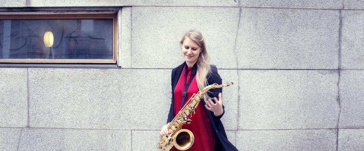 Adele Sauros hymyilee saksofonin kanssa.