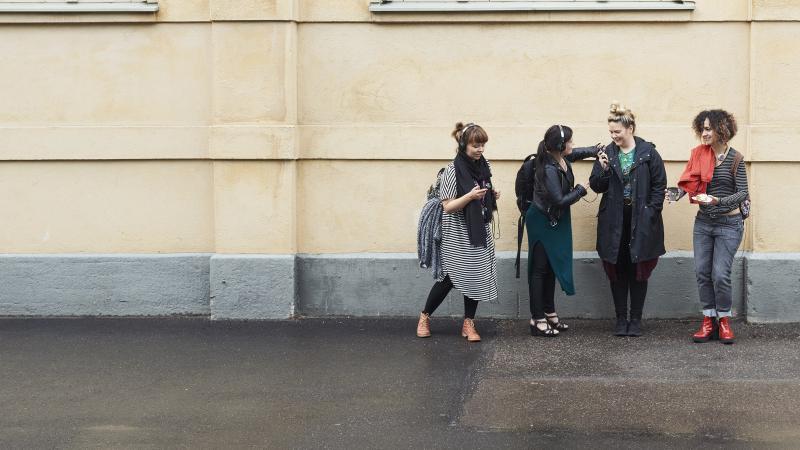 Neljä naista seisoo ulkorakennuksen edessä