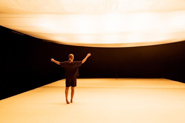 Nainen selin yleisöön näyttämöllä, jossa on valkoinen tanssimatto ja saman värinen kangaskatto.