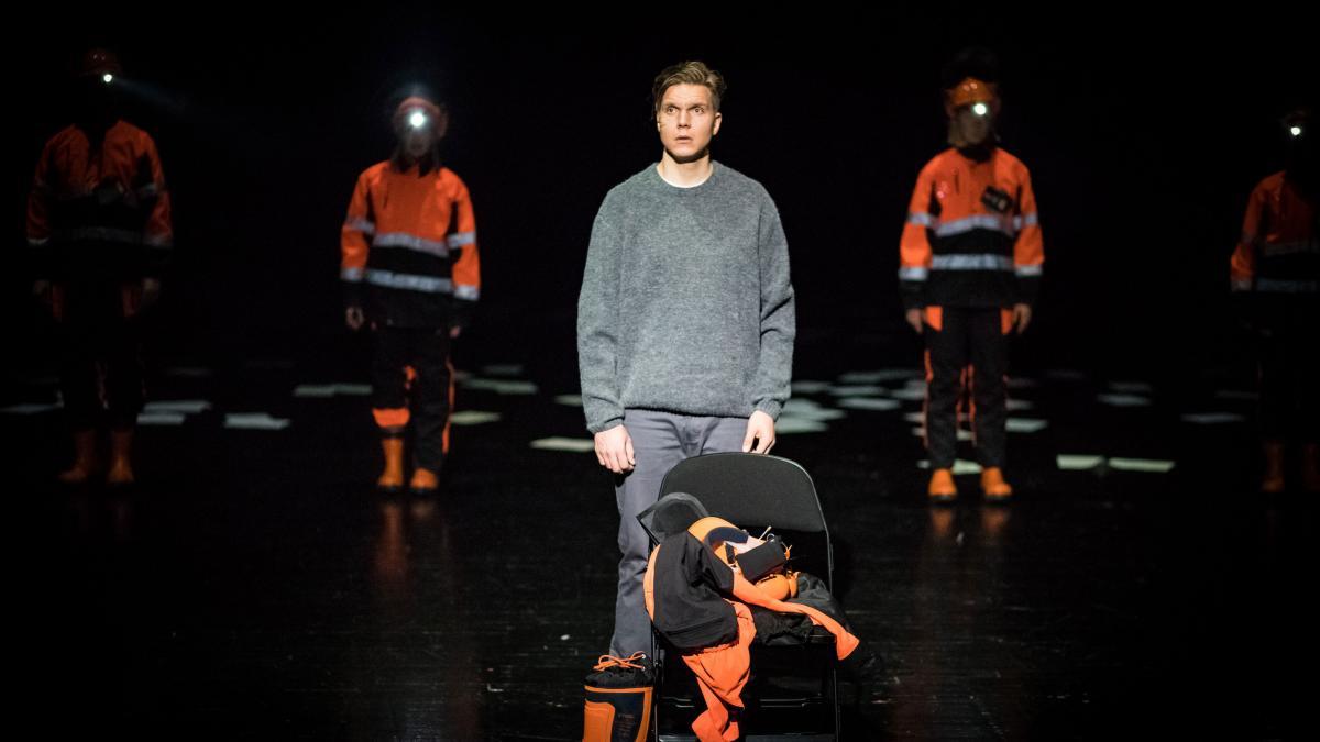 Mies seisoo teatterilavalla ja hänen taustallaan pimeydestä erottuu kaksi metsureiksi pukeutunutta hahmoa.
