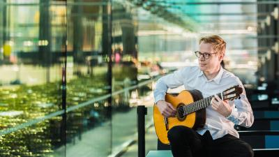 Janne Malinen sits in front of the window wall in the Musiikkitalo café and plays guitar. He looks out and smiles.
