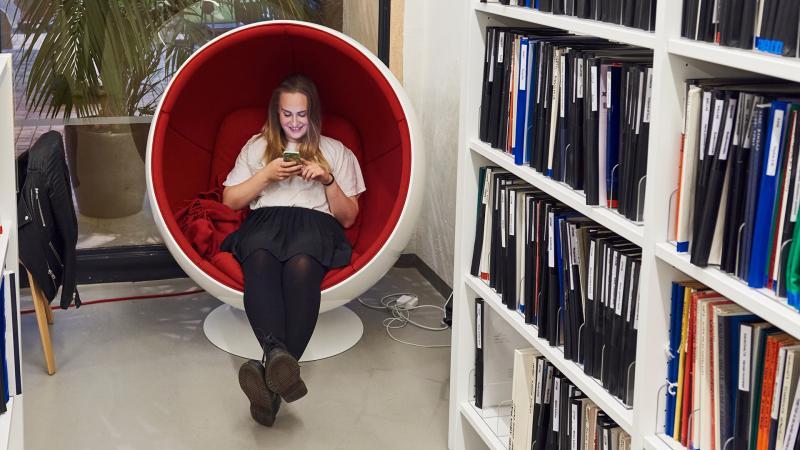 Nuori henkilö istuu kirjastossa pallotuolissa ja selaa kännykkää. Etualalla kirjahylly, jossa julkaisuja.