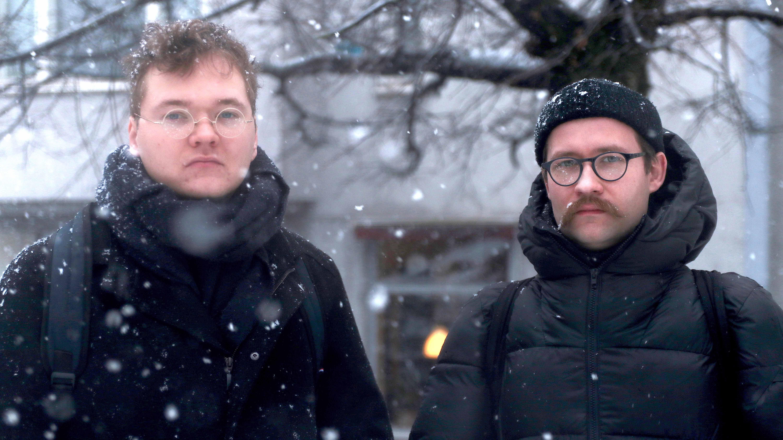 Kaksi miestä seisoo lumisateessa ja katsoo kameraan.