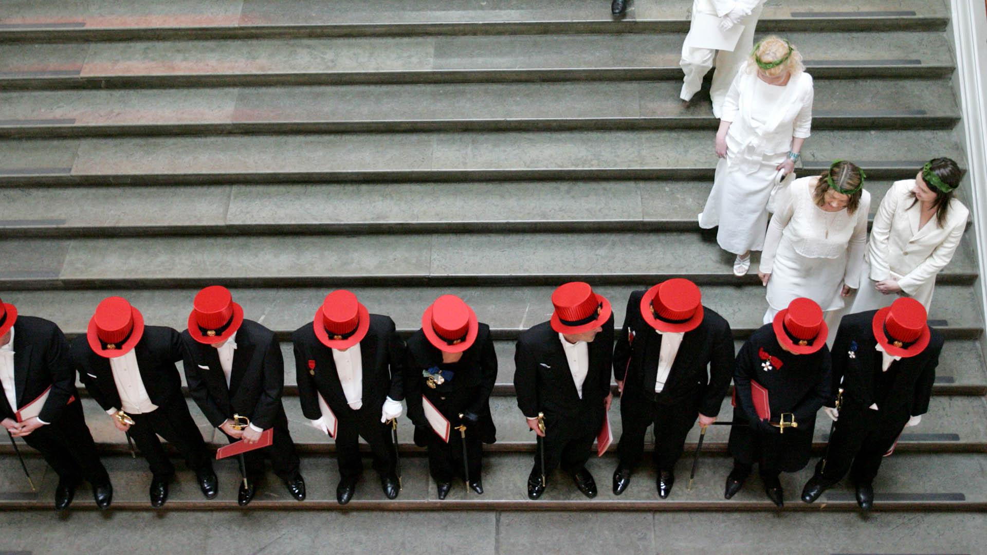 Taideyliopiston promotoituja tohtoreita punaisine hattuineen portailla ylhäältä käsin.
