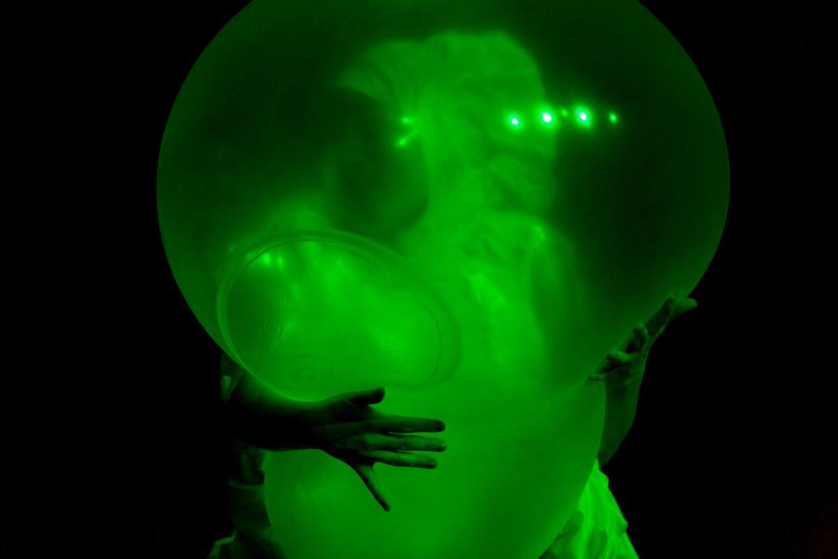 Esiintyjä pitää sylissä itsensä kokoista ilmalla täytettyä läpikuultavaa muovia.