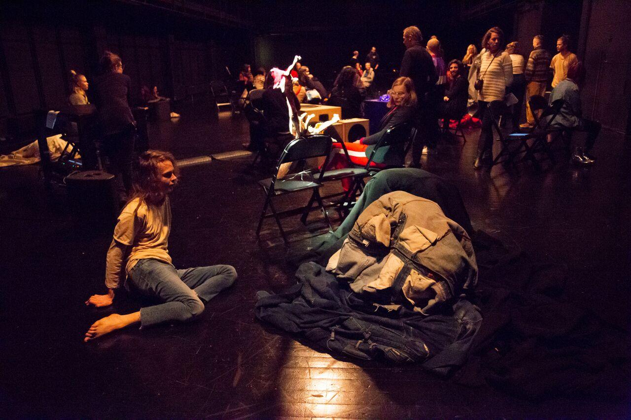 Black box tila, jossa tuoleja, esityksellisiä objekteja ja yleisöä sekaisin.