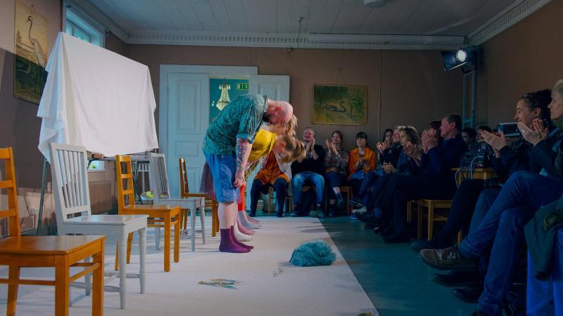 Näyttelijät kumartavat yleisölle isossa huoneessa.