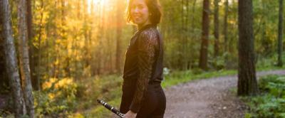 Lucy Abrams poseeraa klarinetin kanssa metsässä ilta-auringossa.