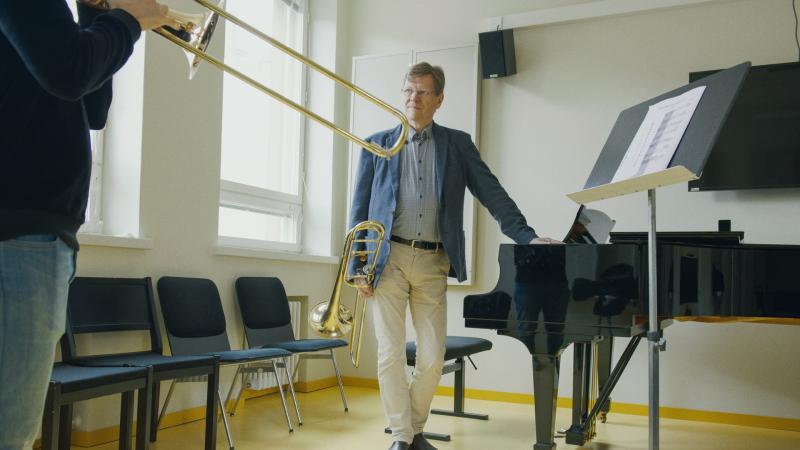 Teacher leans on a piano and follows as his students plays trombone.