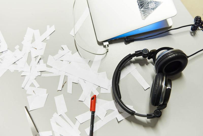 Laptop, pieces of paper and headphones on a table