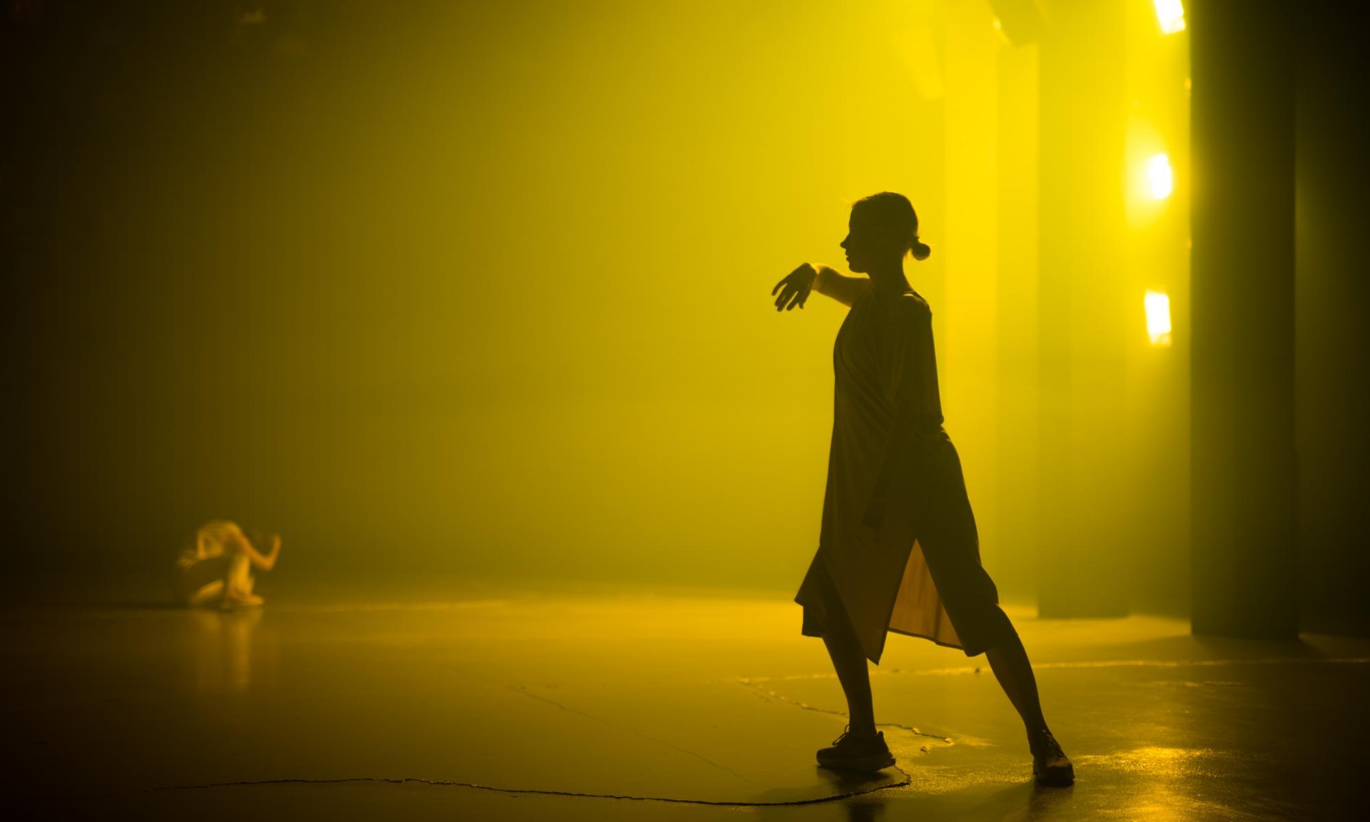 Tanssija keltaisessa, sumun täyttämässä esitystilassa