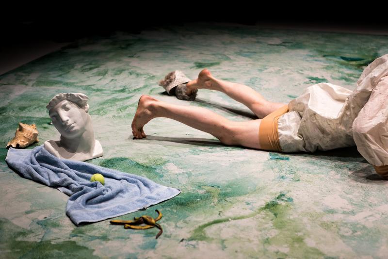Vesivärimaalatulla lattialla kipsipää, pyyhe, tennispallo, banaaninkuori ja ihmisen alaruumis.