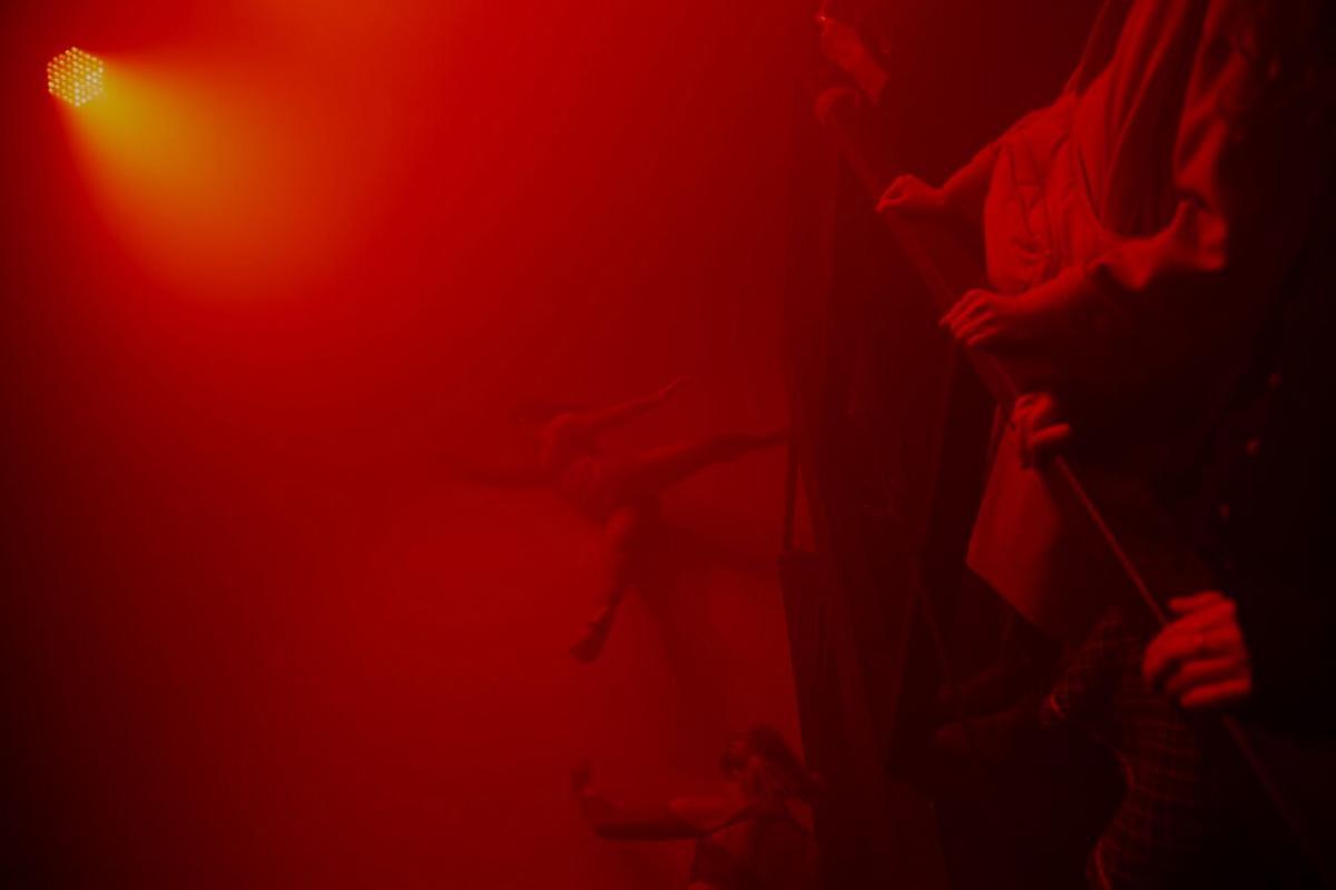 Tanssija lattialla tilassa joka on sakeana sumusta ja kirkkaan punainen. Yleisö katsoo tapahtumaa yläperspektiivistä aidatusta aitiosta.