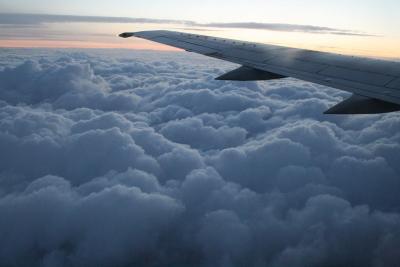 Lentokoneen siipi, taustalla pilviä ja auringonlasku