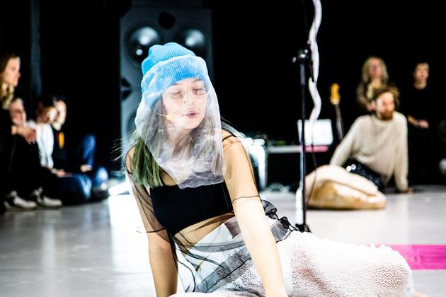 Naisoletettu esiintyjä istuu näyttämöllä päässään sininen pipo ja sen päällä, kasvojen edessä roikkuu huntu, johon on piirretty karkeasti silmät, nenä ja suu.