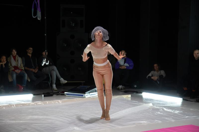 Nainen nojaa eteenpäin selkä yleisöön päinv läpinäkyvän muovin peittämällä näyttämöllä.