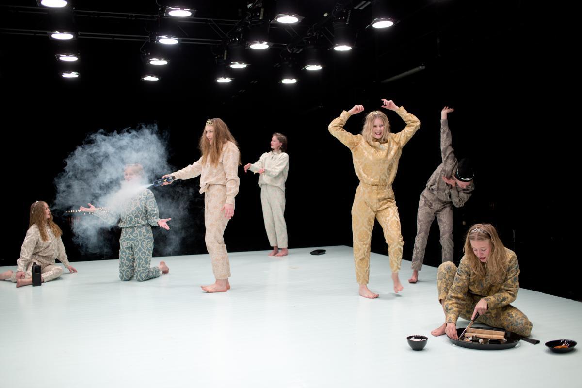 Kokopukuihin pukeutuneet tanssijat tekevät erilaisia tekoja näyttämöllä.