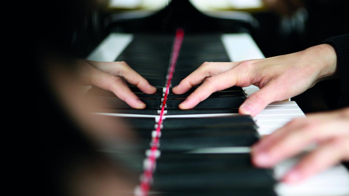 Kädet pianon koskettimilla