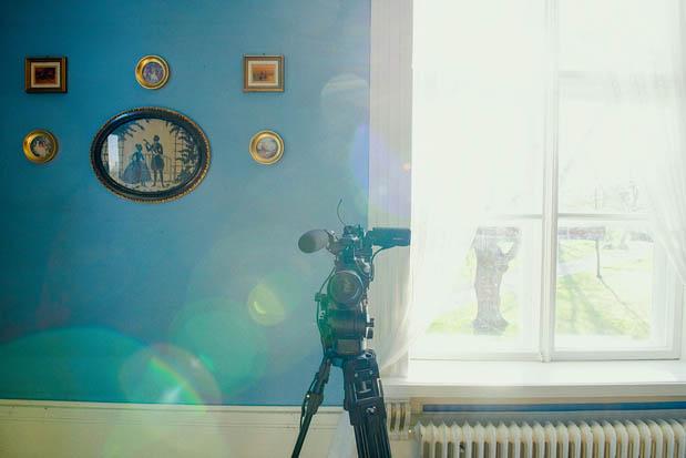 Kamera jalustalla taustalla tauluja seinällä ja ikkuna.