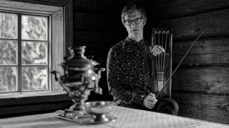 Ilkka Heinonen istuu pirtin pöydän ääressä mustavalkoisessa kuvassa.