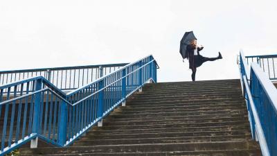 Nainen pitelee sateenvarjoa ja ottaa ison askeleen eteenpäin portaiden yläpäässä.
