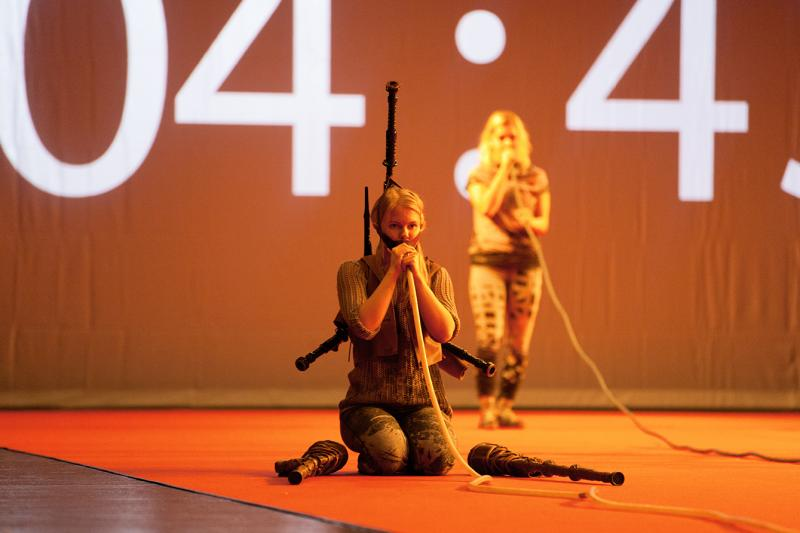 Performer on red stage, bagpipe on her back, blowing to a plastic tube.