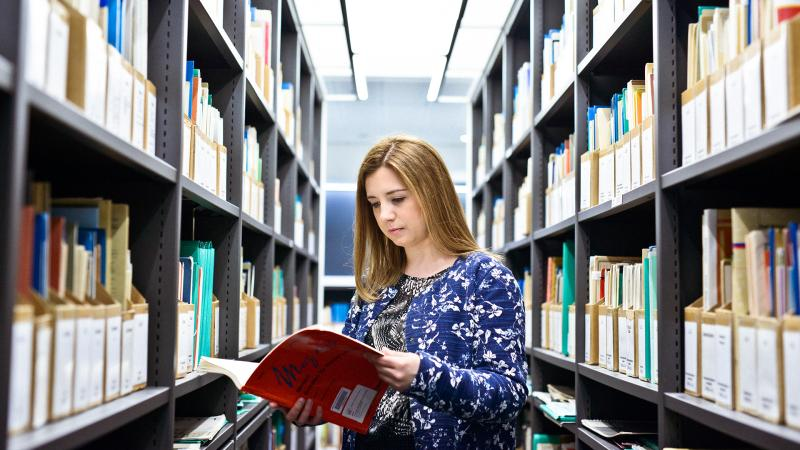 Henkilö selaa kirjaa kirjastossa, seisoo kahden suuren kirjahyllyn välissä.