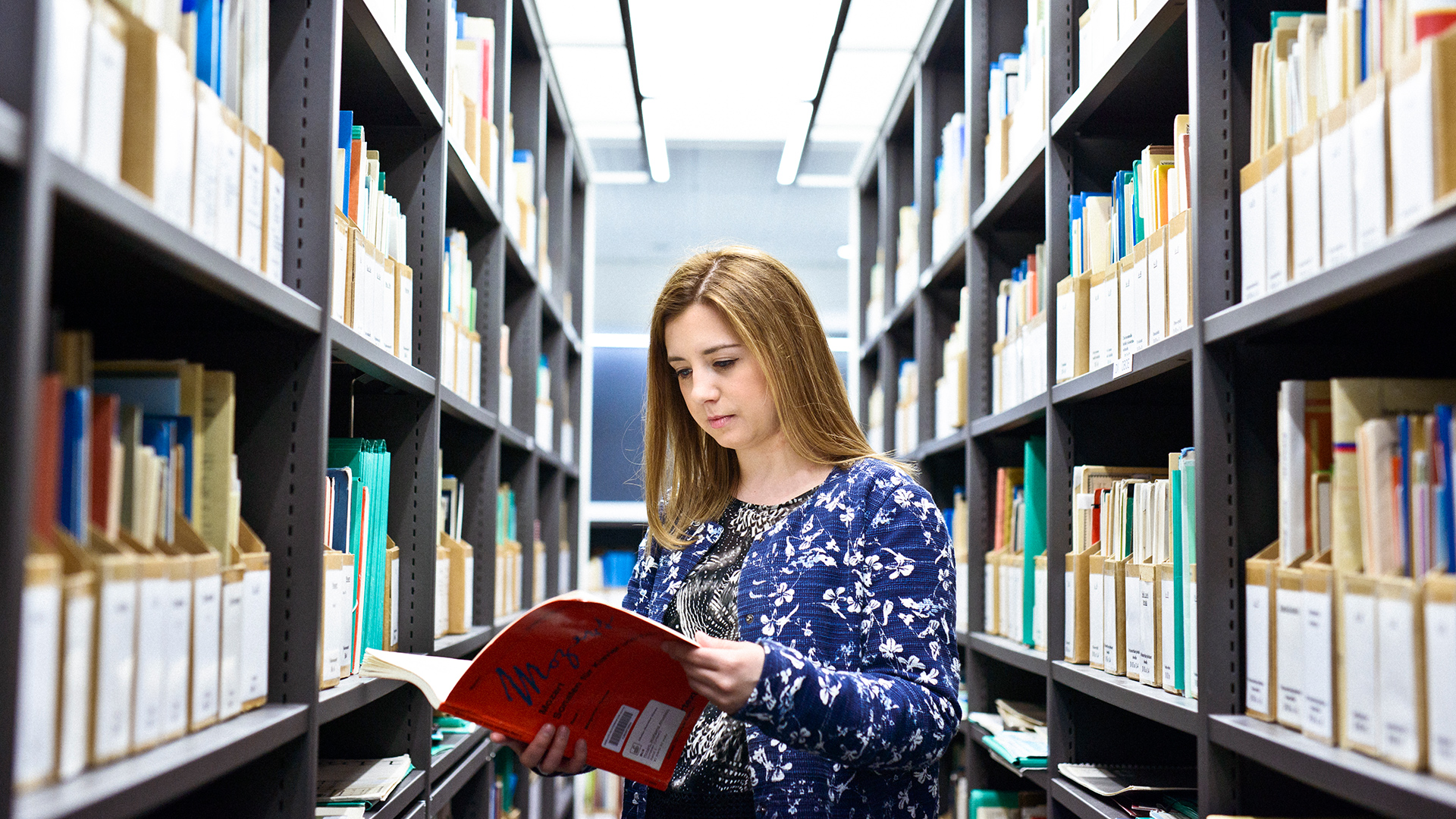 Person in a library browsing through a publication.