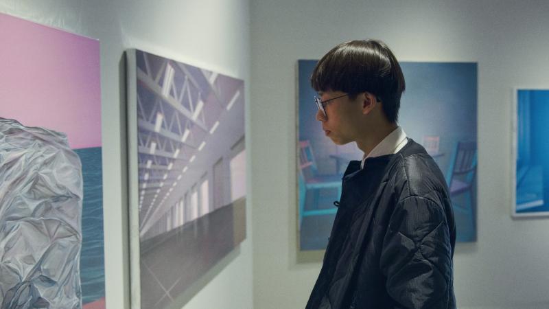 Opiskelija katsoo teosta taidenäyttelyssä.