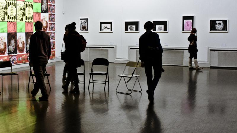 Yleisöä ja taideteoksia näyttelyssä.
