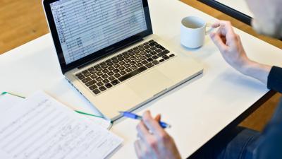 henkilö katsoo kannettavan tietokoneen ruutua tehden muistiinpanoja kynä kädessä