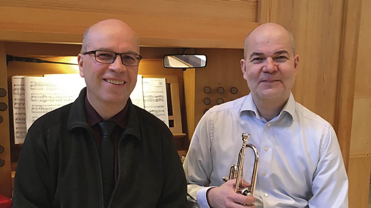 Tapani Heiskanen ja Seppo Kirkinen hymyilevät vierekkäin. Tapanilla on trumpetti käsissään.