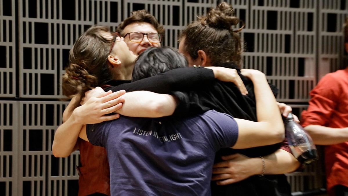Opiskelijoita halaamassa toisiaan harjoitusten keskellä