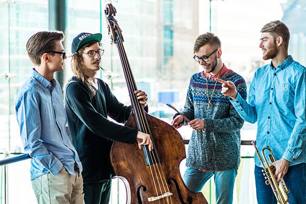 Opiskelijoita soittimien kanssa ikkunan edessä