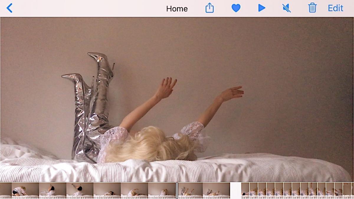 Henkilö makaa sängyllä kädet ilmassa, hopeiset piikkikorkosaappaat jalassa. Kasvoja ja vartaloa ei näy.
