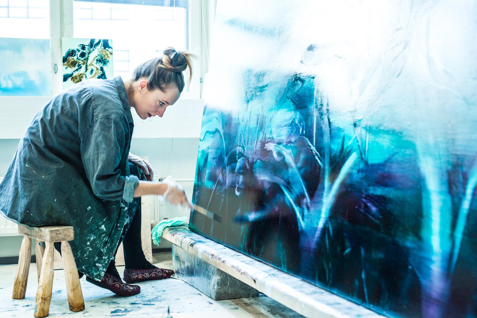 Opiskelija maalaa työhuoneella suurta sinistä maalausta