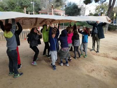 Joukko iloisia lapsia kannattelee päänsä päällä suurta paperia, johon on maalattu kuvioita.