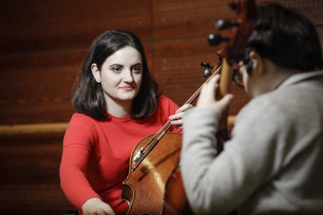 Klassisen musiikin opettaja ohjaa lasta sellon soittamisessa.