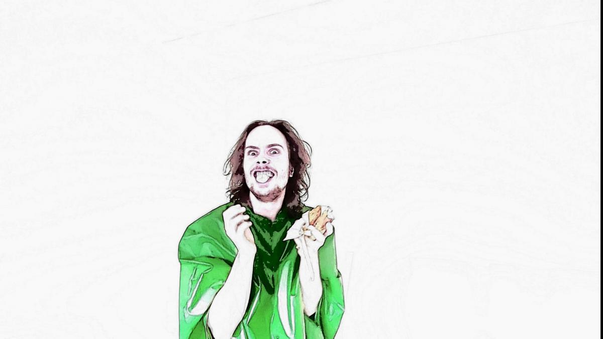 Miesoletettu vihreässä paidassa katsoo kameraan ja irvistää leipä kädessään.