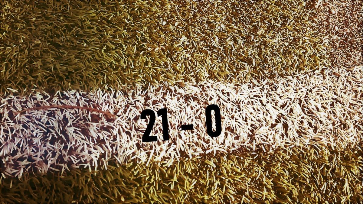Jalkapallokentän valkoisen viivan päällä numerot 21 -0.