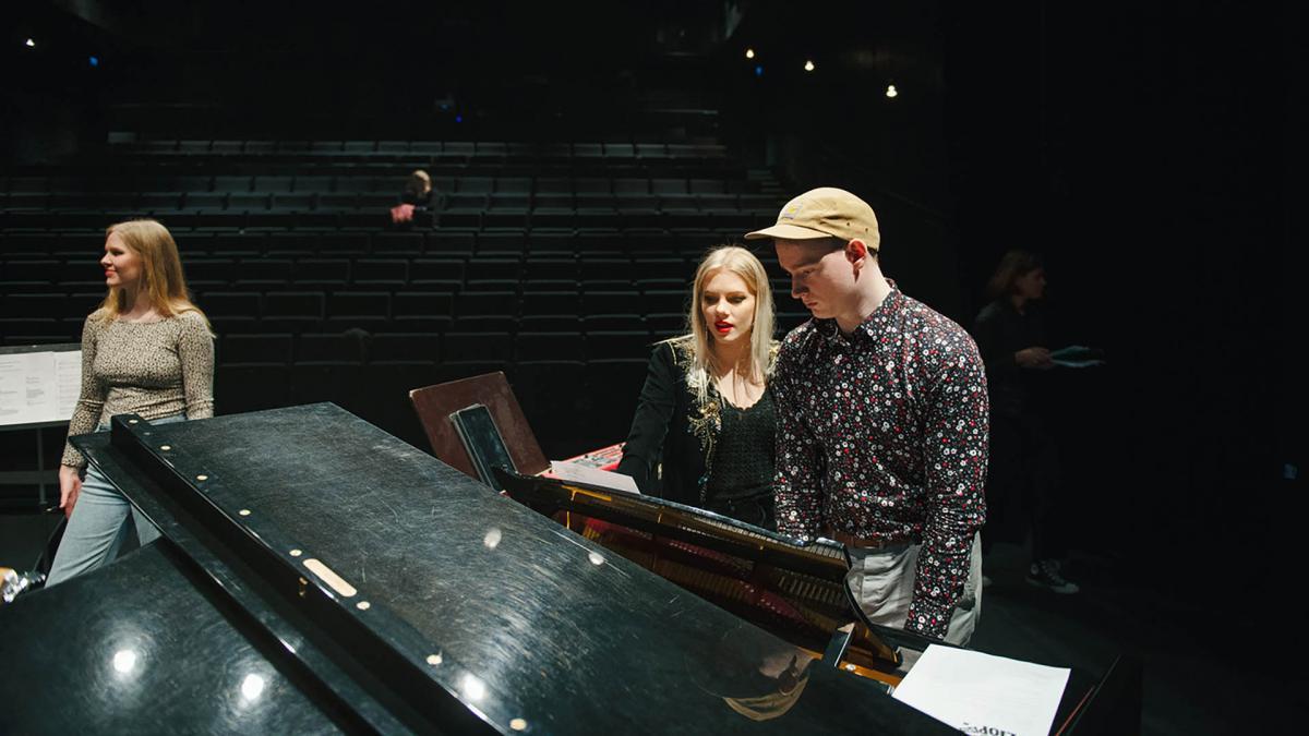 Opiskelijat tutkivat nuotteja pianon ääressä