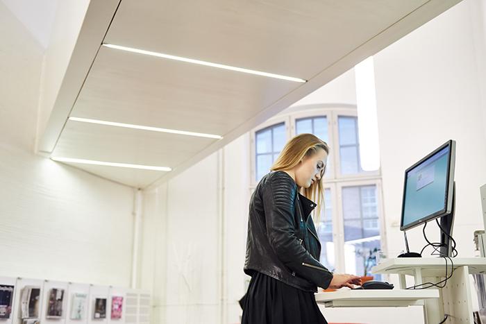 Nainen seisoo tietokonepöydän edessä