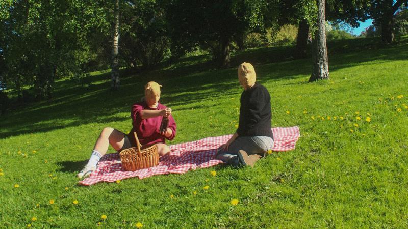 Kaksi henkilöä piknik-viltin päällä kangasnaamiot päässä.