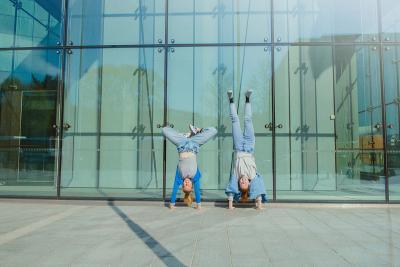 Kaksi henkilöä seisoo päällään lasiseinän edessä