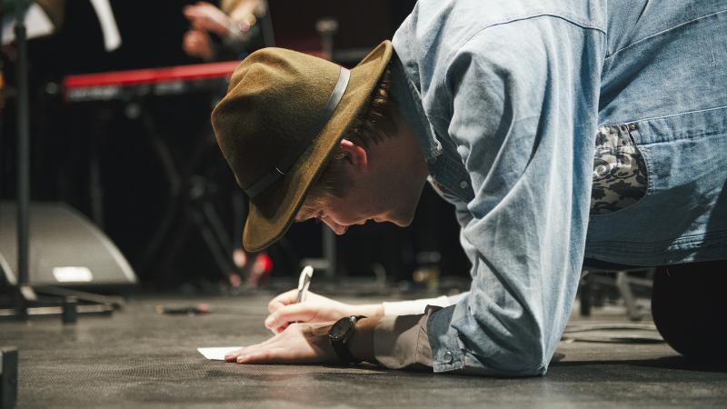 Mies kirjoittaa muistiinpanoja lattialla.