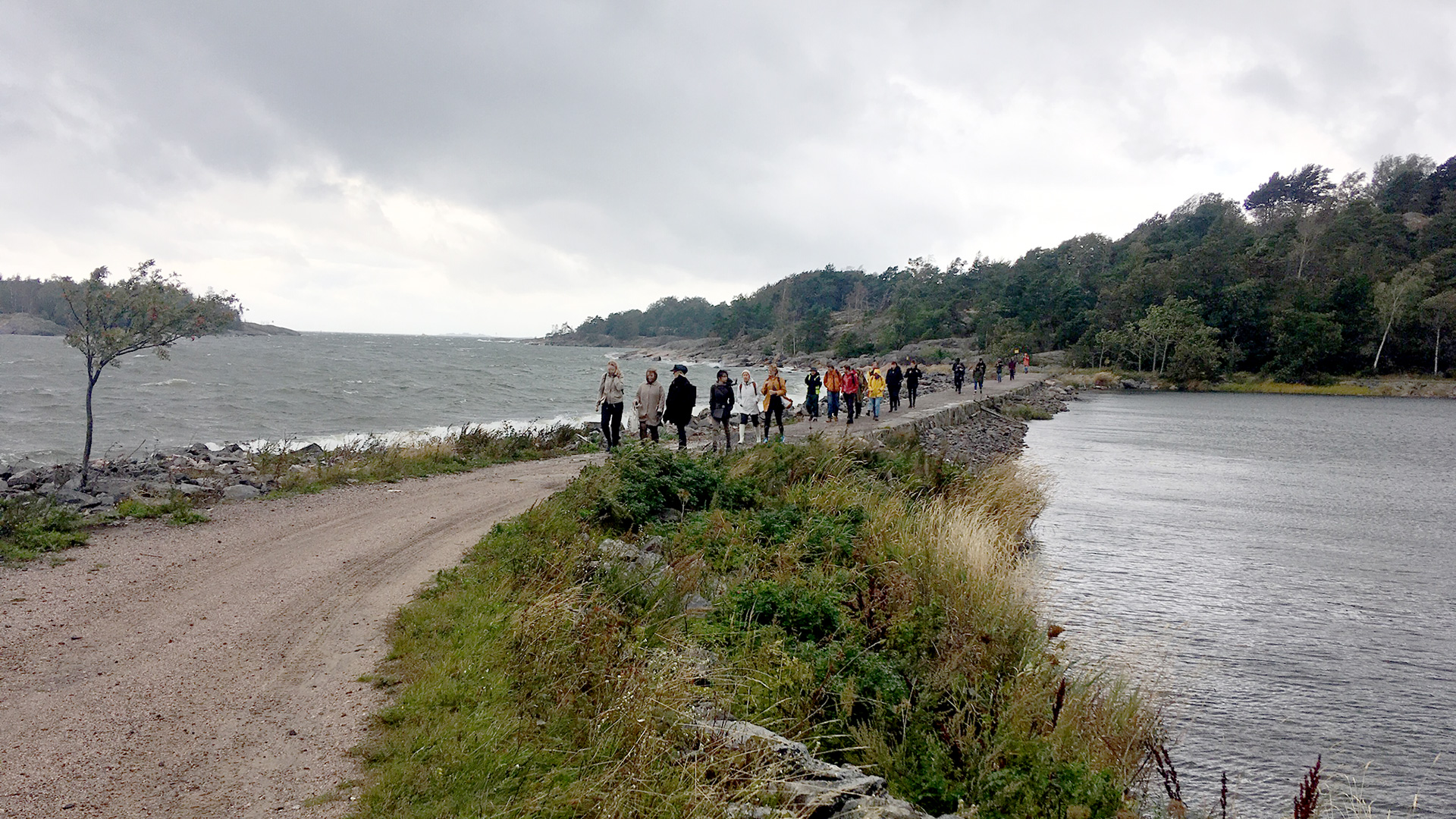 People crossing a neck of land between Vallisaari and Kuninkaansaari islands.