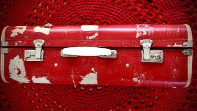 Kuvassa punainen matkalaukku, tausta punainen virkattu