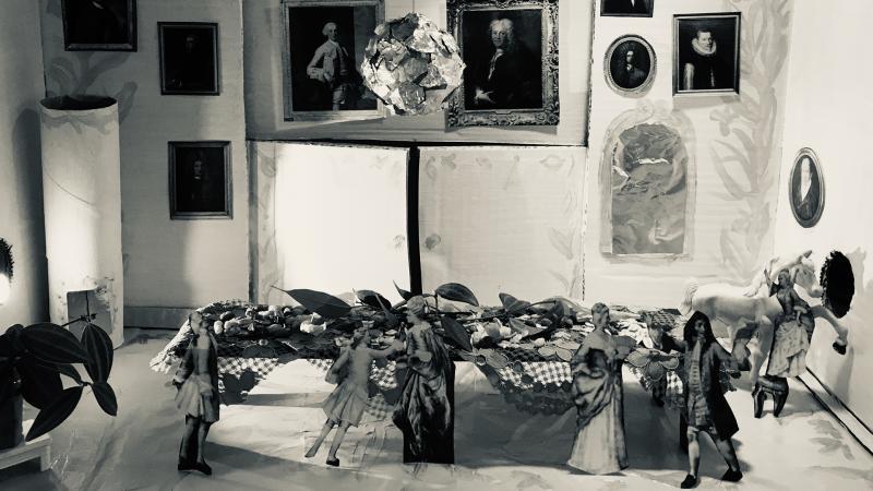 Huone, oikealla pystyuuni, seinällä tauluja, keskellä pöytä, pöydän edessä tanssivia ihmisiä, pöydän sivulla keinuhevonen