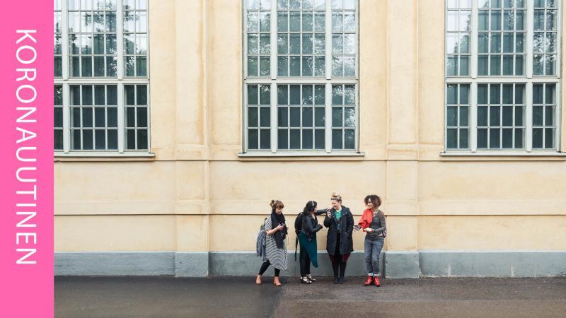 Neljä naista seisoo rakennuksen edessä