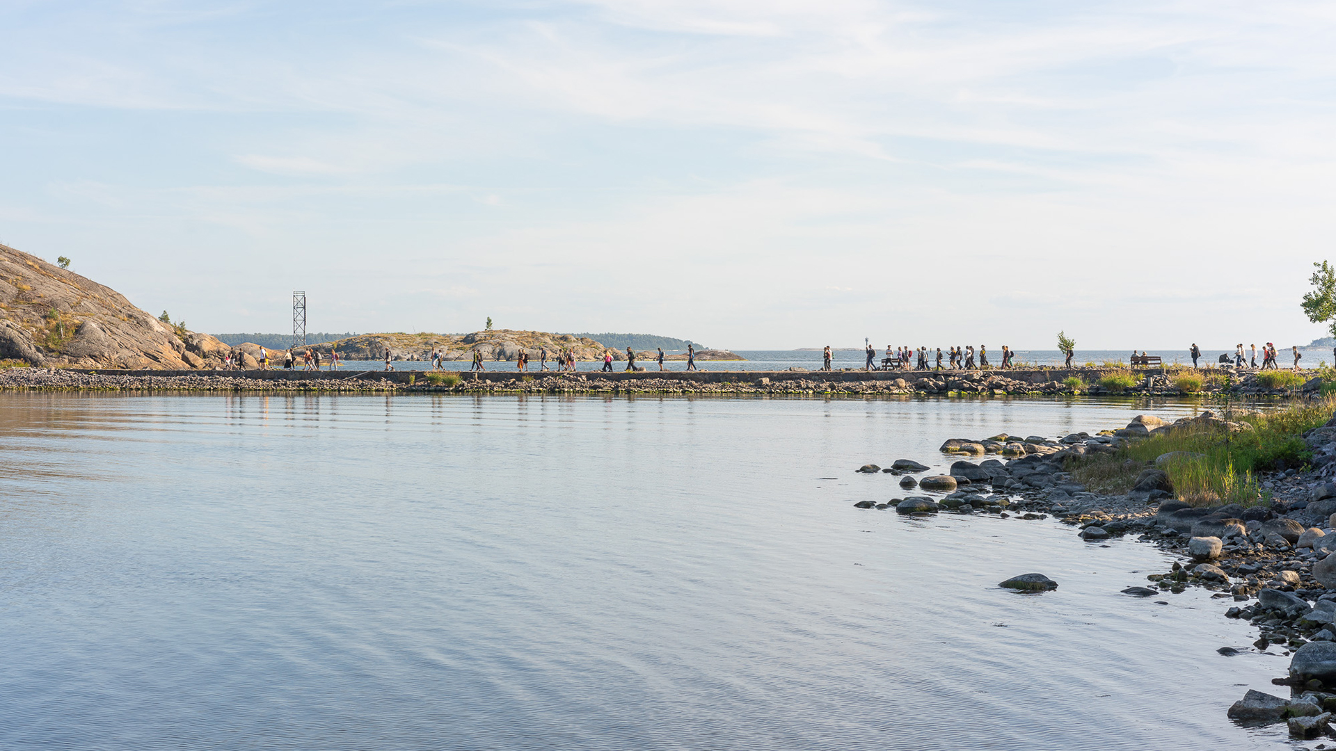 From a distance, people crossing a neck of land that connects Vallisaari and Kuninkaansaari islands.